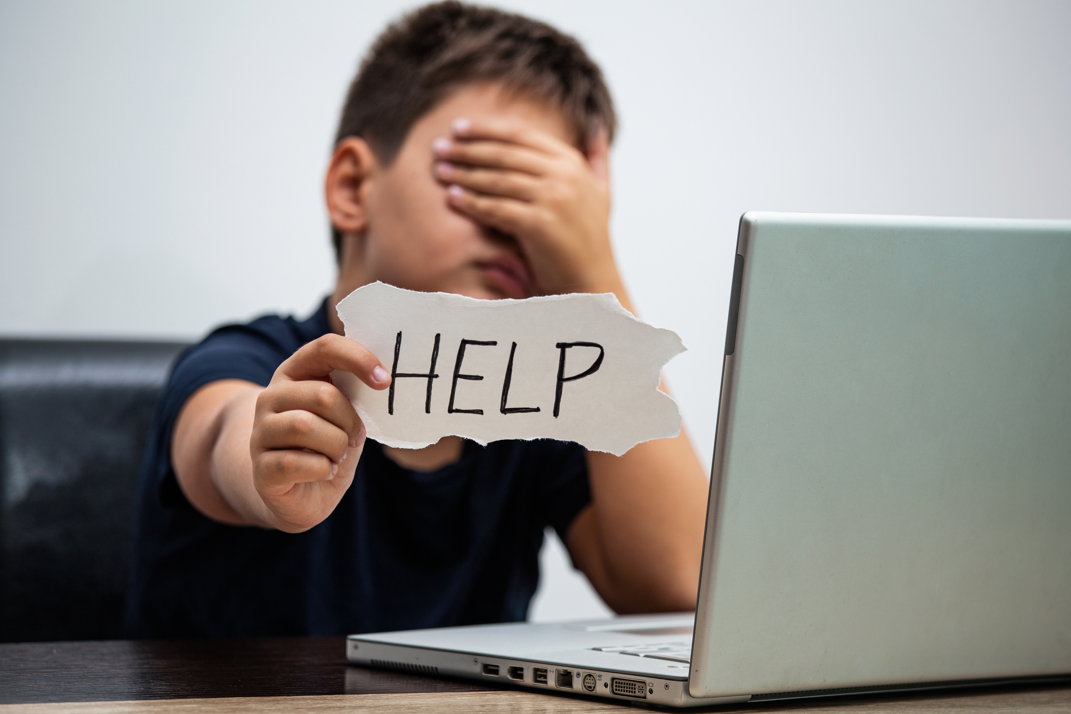 Sad and scared young boy with computer laptop asking for help