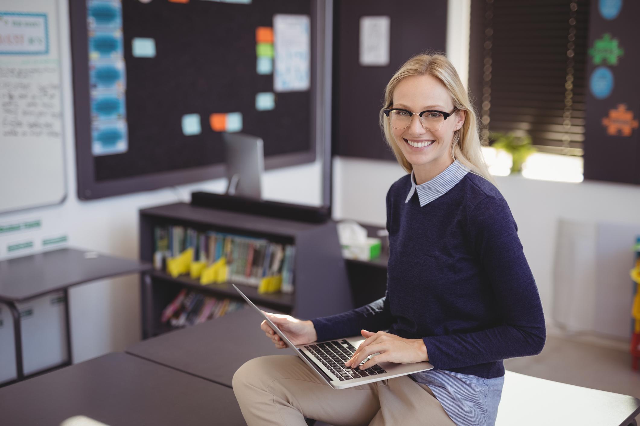 Portrait of happy teacher using laptop in classroom at school